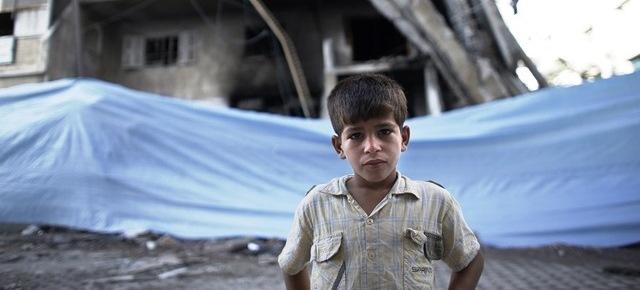 Un bambino fra le devastazioni della guerra