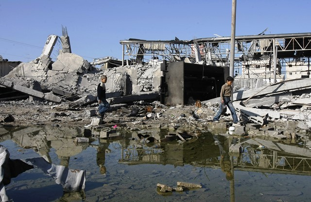 Palestinian boys walk past a destroyed building in al-Zeitun neighborhood following Israeli strikes in Gaza City on January 10, 2009. Israeli troops battled Hamas fighters in Gaza into a third week today as both sides ignored a UN Security Council demand to end the fighting that has killed more than 800 people. AFP PHOTO / MAHMUD HAMS