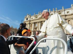Papa Francesco, all'inizio dell'udienza generale, accoglie un bambino sulla Papa mobile