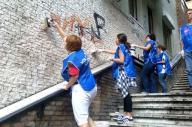 Alcuni volontari, a Roma, ripuliscono un muro