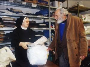 Una suora consegna degli abiti a un senza fissa dimora