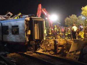 I soccorritori al lavoro, stanotte, fra le lamiere dei due treni scontratisi