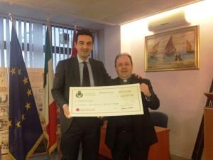 L'assegno di 20 mila euro consegnato dal sindaco Maragno a don Marco Pagniello - foto Comune di Montesilvano