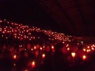 Il palasport buio, illuminato solo dalle candele